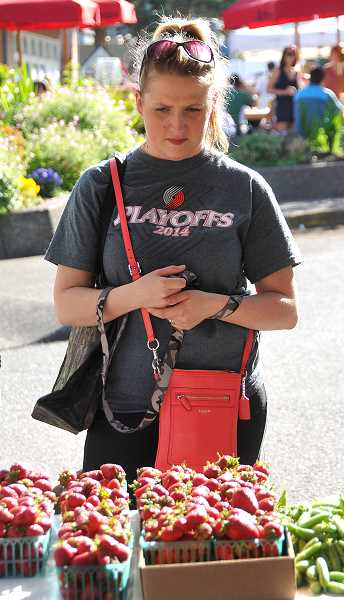 by: TIDINGS PHOTO: VERN UYETAKE - Sheena Burke decides on which strawberries to purchase from Yangs Fresh Bloom farm.