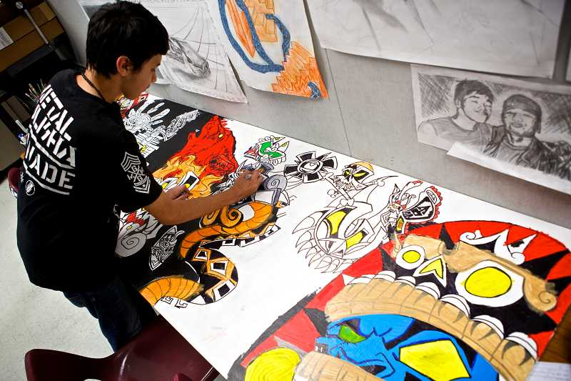 by: TIMES PHOTO: JAIME VALDEZ - Jacob Villanueva who is a freshman at Tualatin High School, works on a mural he created he calls, Quetzalcoatl.