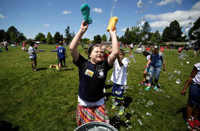 by: TIMES PHOTO: JONATHAN HOUSE - Oak Hills Elementary student Rachel Willins flings soaked sponges over her head during the school's field day.
