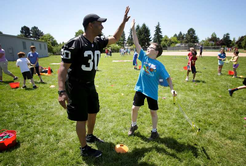 by: TIMES PHOTO: JONATHAN HOUSE - Former NFL player Anthony Newman high-fives Oak Hills Elementary student Ben Johnson after his team scores a goal in a beanbag sling during the school's field day.
