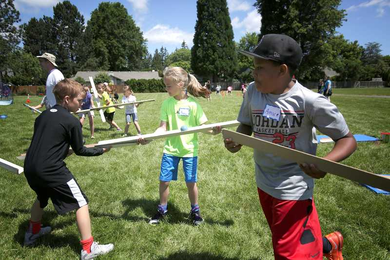 by: TIMES PHOTO: JONATHAN HOUSE - Oak Hills Elementary student Kayla Nelson holds steady to move a ball along, as her teammates frantically race to continue the path in front of it. The exercise was part of the school's annual field day.