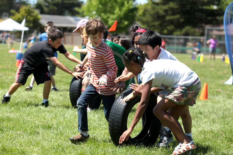 by: TIMES PHOTO: JONATHAN HOUSE - Oak Hills students race with tires as a team during the school's annual field day.