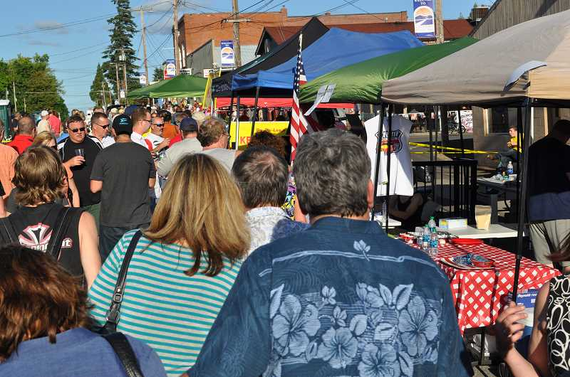 by: NEWS-TIMES PHOTO: MICHELLE THOMAS - North Plains Commercial Street was packed with people last weekend in search of award-winning barbecue last Saturday, though attendees reported food booths had mostly sold out of samples by 6 p.m.