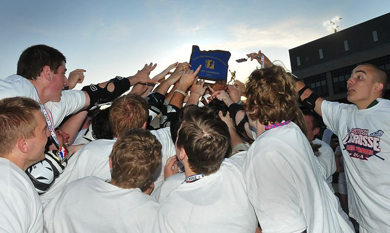 by: VERN UYETAKE - West Linn lacrosse players hoist the state championship trophy at Lake Oswego High School following the team's 13-9 victory over Lakeridge.
