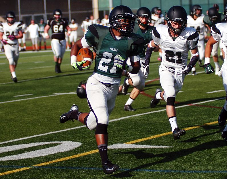 by: DAN BROOD - NO CATCHING HIM -- Tigard High School junior Sam Inos (left) sprints to the end zone for a Green team touchdown during Saturday's Chicken and Bean Bowl. Inos scored four touchdowns in the 52-52 tie.