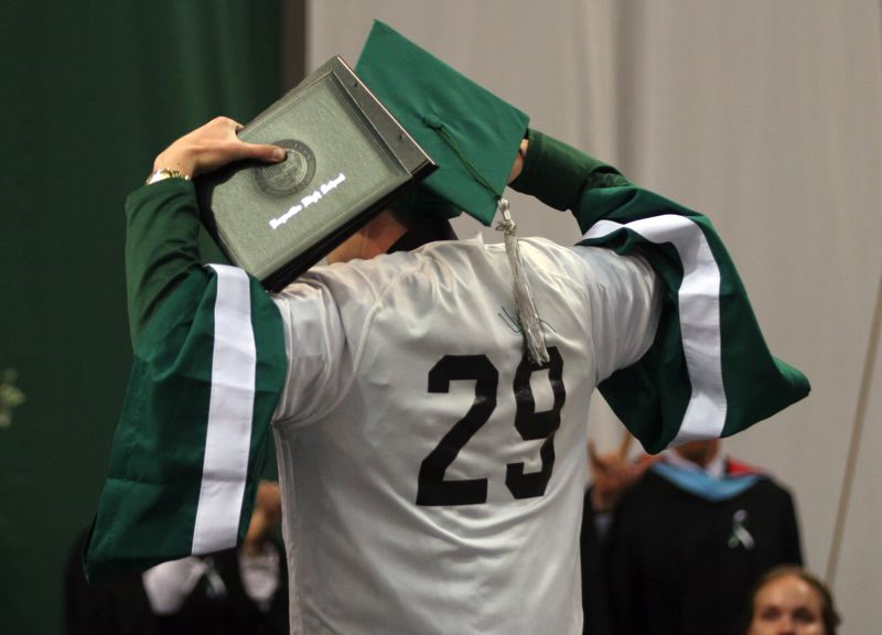 by: OUTLOOK PHOTO: JIM CLARK - After receiving his diploma, Joshua Mitchell turns his back to the crowd and displays the number on Emilios jersey, which he wore over his graduation gown. The entire audience and graduating class rose to their feet and roared.