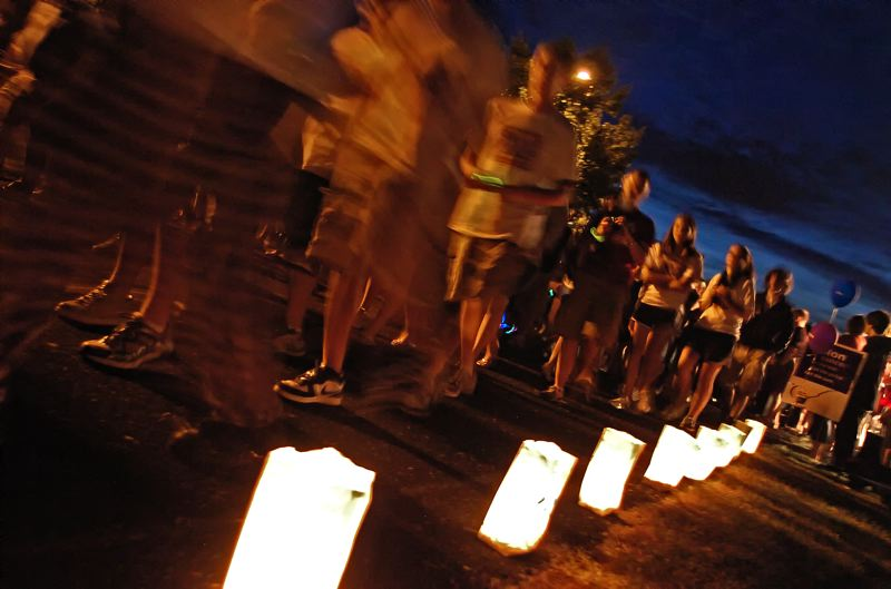 by: SPOKESMAN FILE PHOTO: JOSH KULLA - Walkers circle the Wood Middle School track as Luminaria bags honor cancer victims during an earlier Wilsonville Relay For Life.