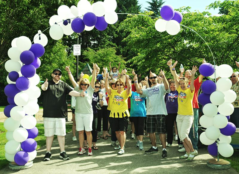 by: SPOKESMAN FILE PHOTO: JOSH KULLA - 2012 Wilsonville Relay For Life participants celebrate at the finish line in Town Center Park, the first year the event was held at that location.