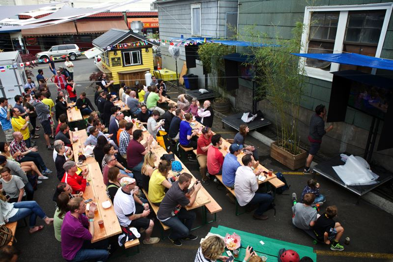 by: TRIBUNE PHOTO: JAIME VALDEZ - Soccer fans watch the opening World Cup Beer Garden match between Brazil and Croatia at the pop-up soccer beer garden in Northwest Portland. Its one of several places around the city hosting World Cup viewing events.