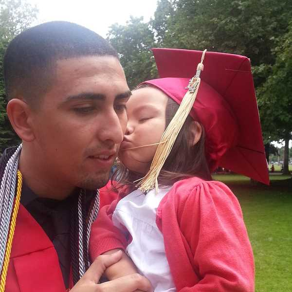 by: SUBMITTED - Anthony Medina's daughter, Adaleah, gives him a kiss to congratulate him on his recent graduation from Western Oregon University.