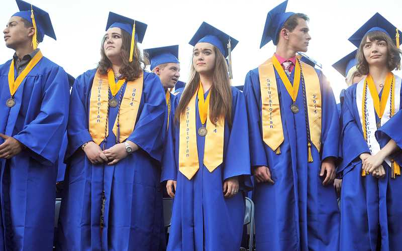 by: FILE PHOTO - Overachiever - Cassidy Helikson stands during graduation ceremonies June 6 at Newberg High School. Helikson, who will attend California Lutheran on a full-tuition music scholarship, graduated in just three years.