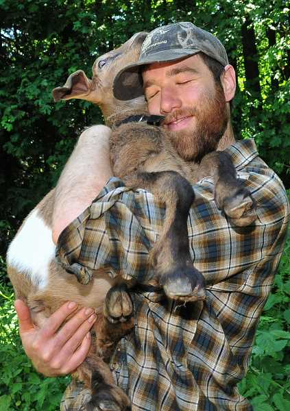 by: REVIEW, TIDINGS PHOTO: VERN UYETAKE - Ian Lamb, goatherd at Tryon Life Community Farm, gives a big hug to one of his beloved goats. Lamb has turned the farm into a goat Garden of Eden.
