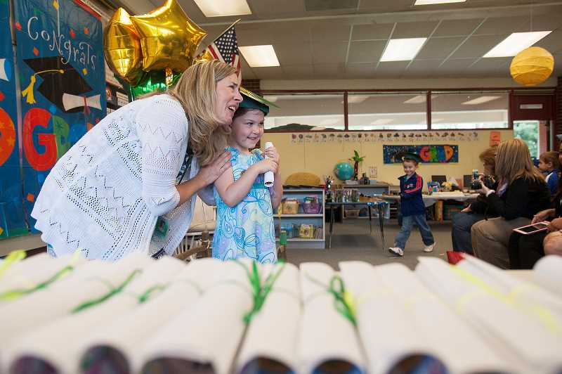 by: PAMPLIN MEDIA GROUP: JOSH KULLA - Cedaroak kindergarten teacher Heather Boyer pauses for a photo as student Hannah Griggs clutches her diploma.