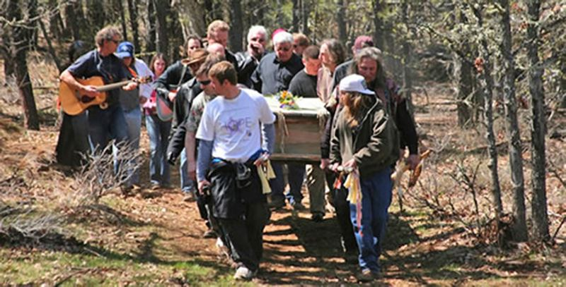 by: PHOTO COURTESY: ELIZABETH FOURNIER - Friends and family take part in a DIY burial by carrying Ray to a grave dug by his grandson on Rays rural Clackamas County property.