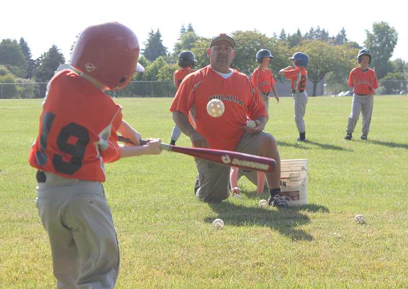 by: JIM BESEDA/MOLALLA PIONEER - Mohicans' assistant Doug Swain serves up wiffle balls during batting practice before a recent CCJBA Midget National game at Clark Park.