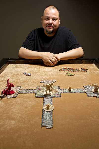 by: TIMES PHOTO: JAIME VALDEZ - Geoffrey Penent, co-owner of Friendly Local Game Store, sits at a custom-made game table with a Descent board game. Besides selling popular game board games, the store features  game rooms for customers.