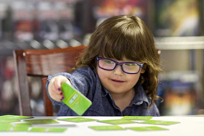by: TIMES PHOTO: JAIME VALDEZ - Madi Karr, 4, who is the niece of Geoffrey Pement, co-owner of the Friendly Local Game Store, plays a memory game at the Beaverton gaming business.