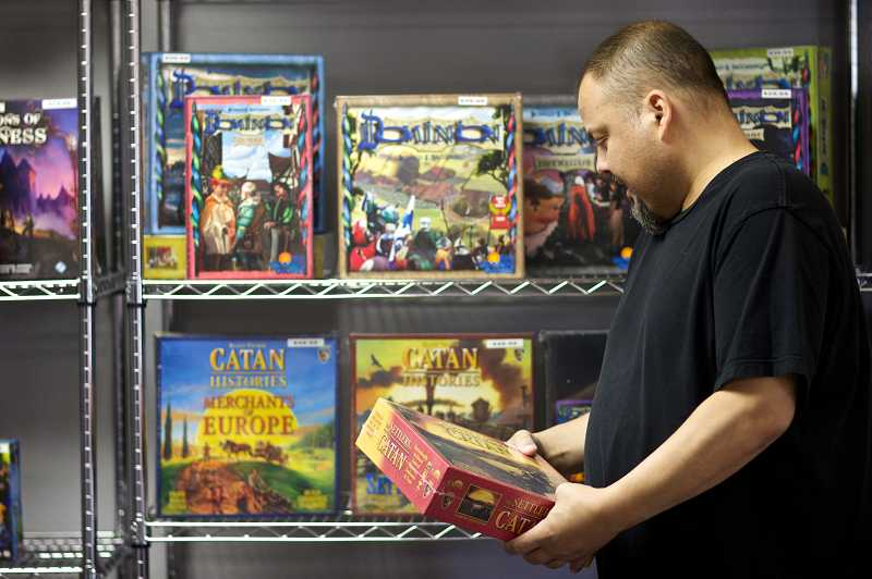 by: TIMES PHOTO: JAIME VALDEZ - Geoffrey Penent, co-owner of Friendly Local Game Store, sells the popular board game, Catan, at the new game store in Beaverton.