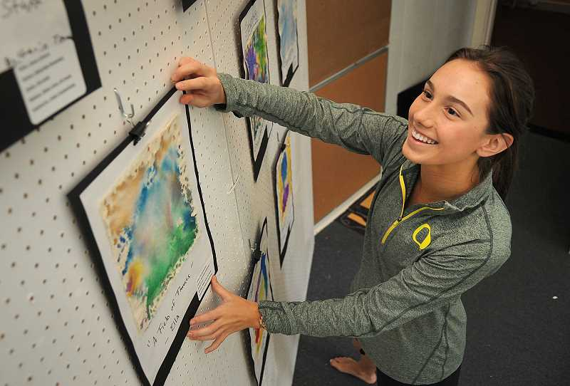 by: REVIEW PHOTO: VERN UYETAKE - Hannah Slauson, a senior at Lakeridge High School, hangs a painting for the elementary school exhibit. Slauson has been helping at the exhibit since she was 11 years old.