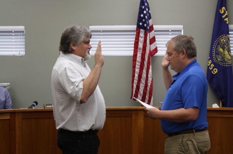 by: SPOTLIGHT PHOTO: ROBIN JOHNSON - Richard Riffle (left) is sworn in to the Scappoose City Council by Mayor Scott Burge at a Monday, June 16, special meeting.