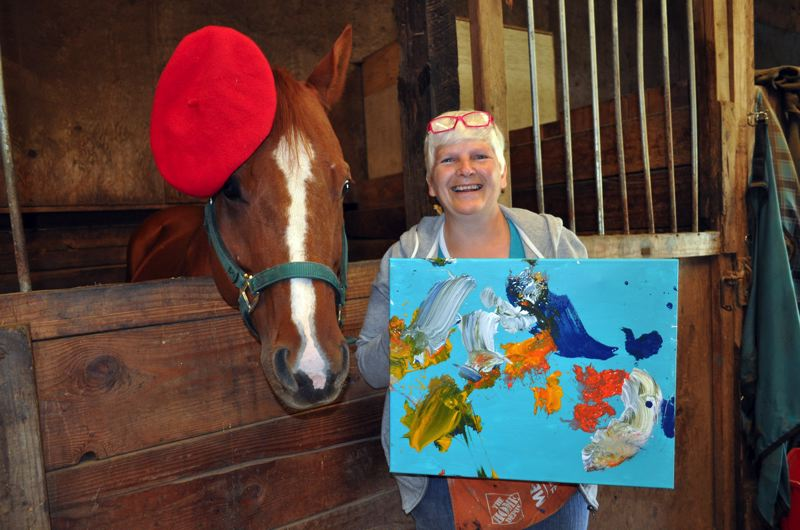 by: HILLSBORO TRIBUNE PHOTOS: MICHELLE THOMAS - Debbie Stanek shows off one of the artworks created by Levi. The horses paintings help to pay his expenses -- including hay, vet and farrier bills and board at Forest Groves Still Waters Stables -- which are also partly offset by a lease agreement to 4-H rider Kayla Raichart.