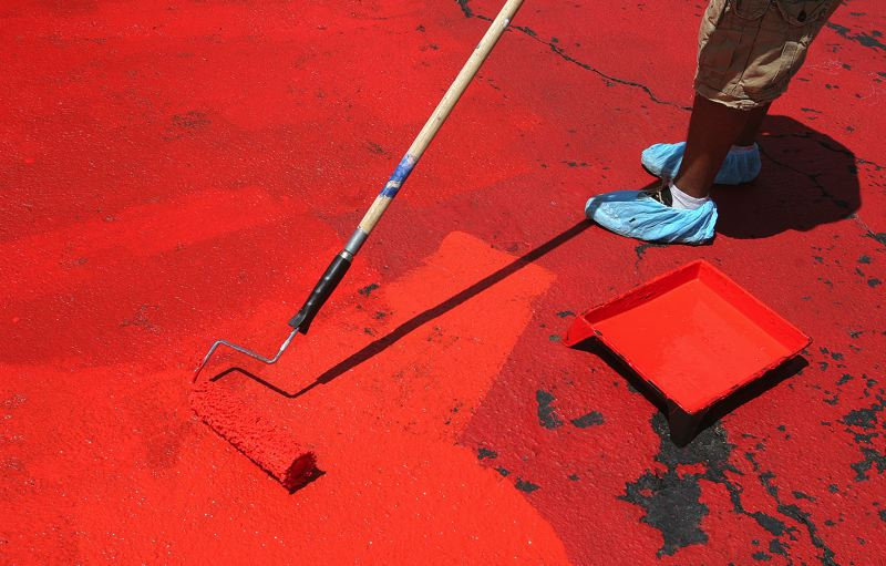 by: OUTLOOK PHOTO: JIM CLARK -  A volunteer uses a roller to paint the large sections of red paint on the Plaza del Sol mural in Rockwood on Friday.