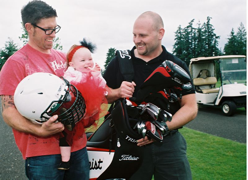 by: JOHN DENNY - Oregon City High School alumnus Jon Hummel (left) and West Linn alumnus Dave Norman get acquainted with Rylee Ferro as they gear up for the 2014 Battle for the Bridge. Rylee, who was diagnosed with Cystic Fibrosis shortly after birth, will be the honorary captain for Oregon City at this years Battle for the Bridge Oregon City vs. West Linn alumni football game. Battle for the Bridge has added a golf tournament to this years festivities, which benefit the Oregon chapter of the Cystic Fibrosis Foundation.