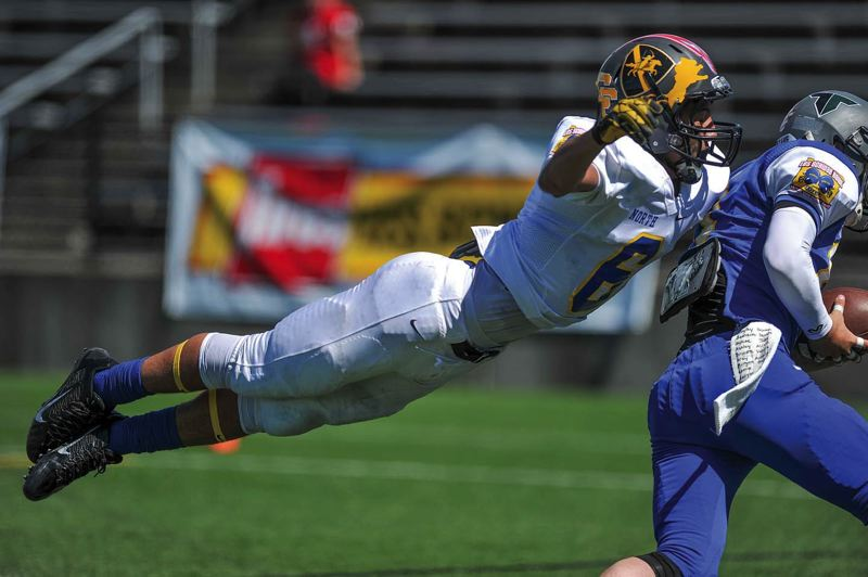 by: COURTESY OF JOHN LARIVIERE - North defensive back James Schell-Buchanan of Roosevelt High takes flight in an attempt to tackle South wide receiver Taylor Travess in the fourth quarter at Hillsboro Stadium.
