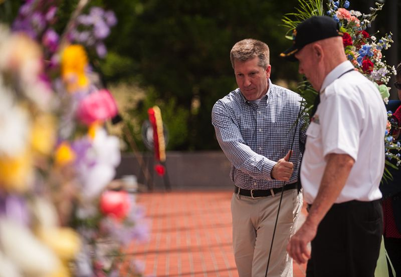 by: SPOKESMAN PHOTO: JOSH KULLA - Wilsonville City Councilor Scott Starr helps place a commemorative wreath at Wilsonville's Korean War memorial at a June 21 ceremony to mark the 1950 start of the war.