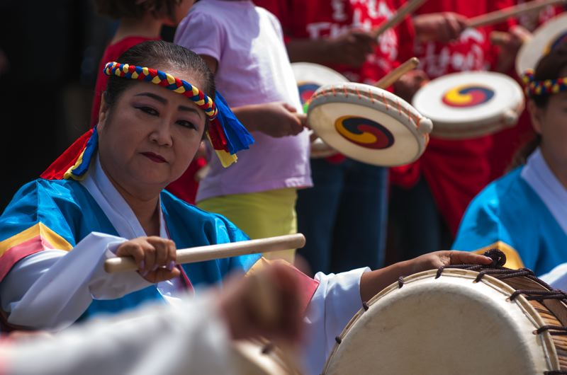 by: SPOKESMAN PHOTO: JOSH KULLA - A drummer from the Oregon Korean Culture Art Center's drum group performs June 21 at Wilsonville's Town Center Park.