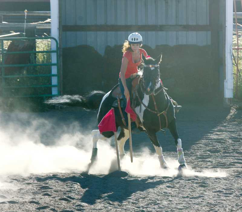 by: JEFF WILSON/THE PIONEER - Taylir Wills urges her horse toward the finish line after picking up a flag.