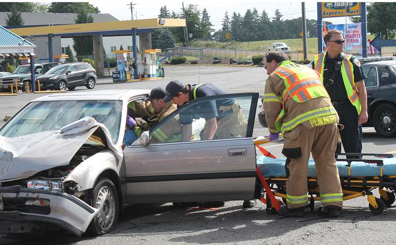 by: JIM BESEDA/MOLALLA PIONEER - Molalla Police Chief Rod Lucich (far right) inspects the scene of a two-car accident at the Y-intersection near the east end of Main Street on Friday, June 20 as emergency personnel with Molalla Rural Fire District No. 73 assist the driver of a Honda Accord that collided with a Dodge Ram 2500.