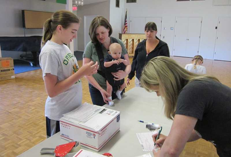 by: BARBARA SHERMAN - BUSY DAY - In the King City Clubhouse, Jennifer Lamaye (center) with baby Jordan, helps volunteers pack boxes before taking them to the Tigard Post Office for mailing.