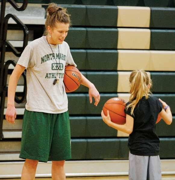 by: PHIL HAWKINS - North Marion assistant girls basketball coach Kelsey Kahle coaches and encourages one of dozens of participants at the Huskies girls basketball camp last week.