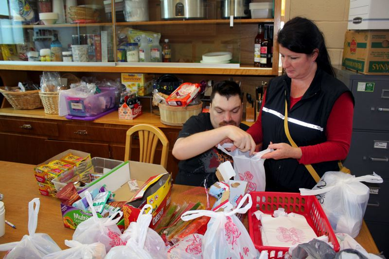 by: POST PHOTO: KYLIE WRAY - Nathan and Denise come in once a week to volunteer at the Action Center. Nathan loves kids, so the two of them assemble snack bags for families that come in with kids.