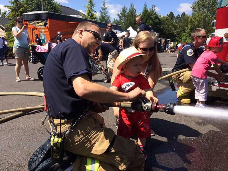 by: COURTESY OF TUALATIN VALLEY FIRE & RESCUE - A young volunteer gets some pointers on how to correctly hose down a fire by a Tualatin Valley Fire & Rescue volunteer.