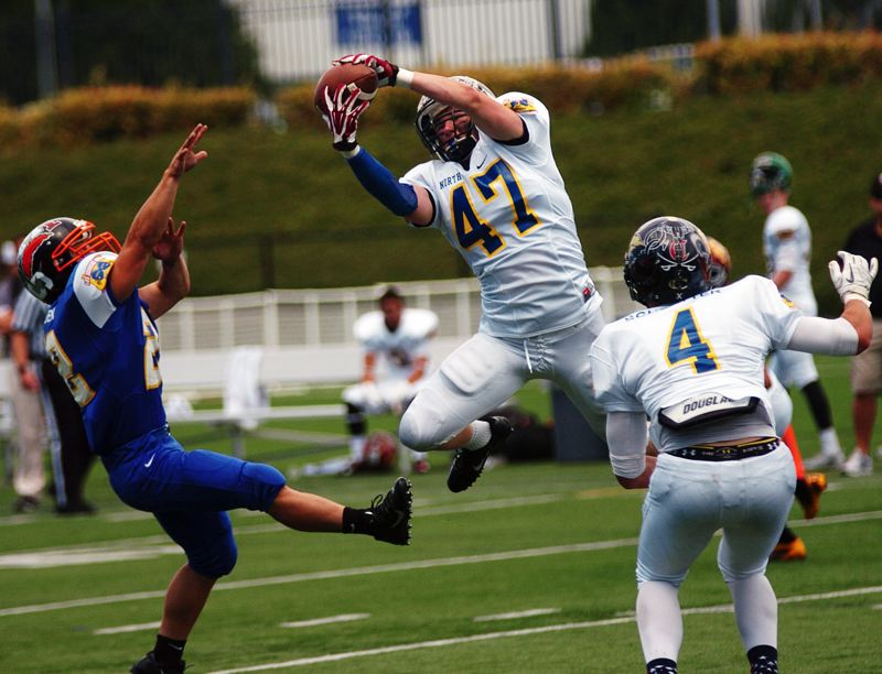 by: DAN BROOD - PICKED OFF -- Sherwood High School graduate Jake Reimer (47), a linebacker for the North team, makes a spectacular interception during Saturday's Les Schwab Bowl. Reimer also had a fumble recovery in the game.