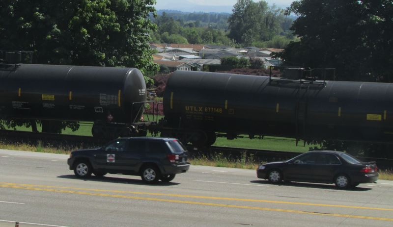 by: MARK MILLER - A unit train of DOT-111 tank cars carrying crude oil parked on the train tracks south of Havlik Road in Scappoose. The train began moving again within 15 minutes or so of stopping.