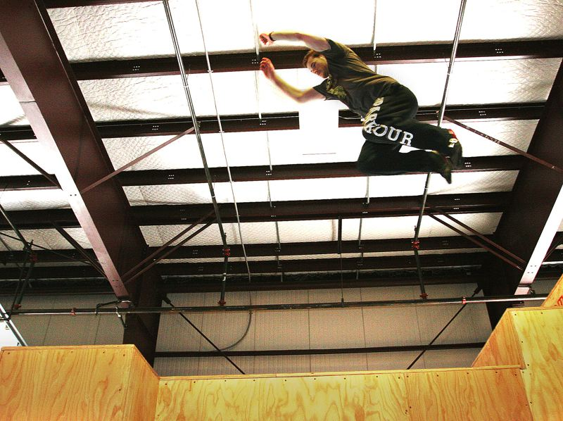 by: OUTLOOK PHOTO: JIM CLARK - Matt Antis, co-owner of Revolution Parkour, leaps through the air inside the new Gresham parkour warhouse facility at 1618 N.E. Eighth St.