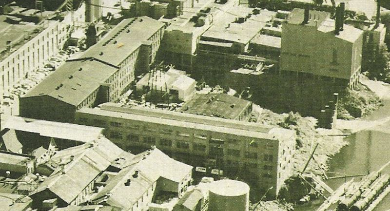 by: PHOTO COURTESY: PUBLISHERS PAPER - A mid-century photo from the cover of a Publishers' Paper Tour Guide shows the 1917 Mill O Building, foreground, with its huge windows on the north side. To the left is the Woolen Mills, and behind MIll O is the 1903 Woolen Mills pullery / picking warehouse.