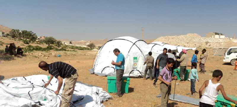 (Image is Clickable Link) Volunteers set up SheleterBox tents in Syria. The humanitarian group provides shelter and equipment to those involved in disasters.