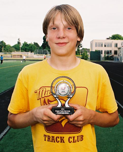by: JOHN DENNY - Arthur Katahdin of Milwaukie proudly displays his hardware for finishing as the high-point 12-and-under male athlete at the recent USA Track and Field State Club Championship Track and Field Meet.