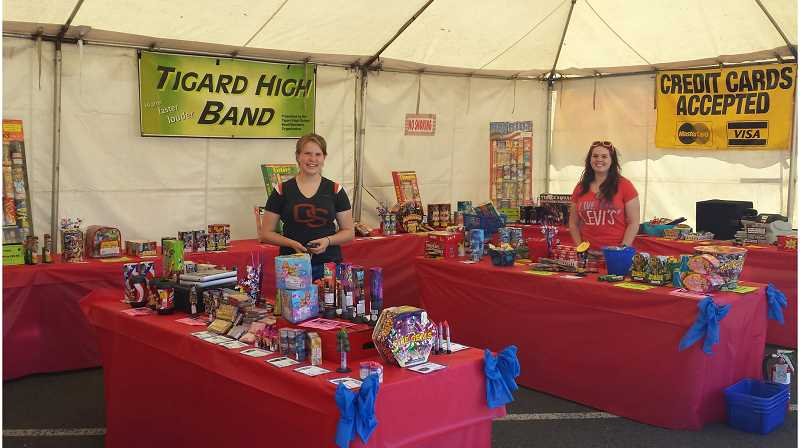 by: JILL WISEMAN - Tigard High School students Julie Otis and McKenna Wiltbank work the fireworks stand on Highway 99W. The school's band program has been selling fireworks every Fourth of July for 20 years.