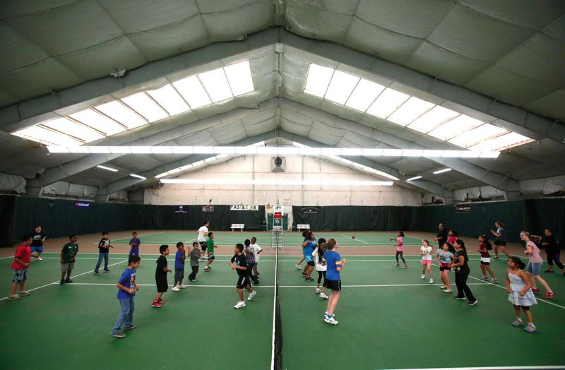 by: TRIBUNE PHOTO: JONATHAN HOUSE - Children in the Portland After School Tennis and Education program at St. Johns Racquet Club dance to Gangnam Style as a way to warm up.