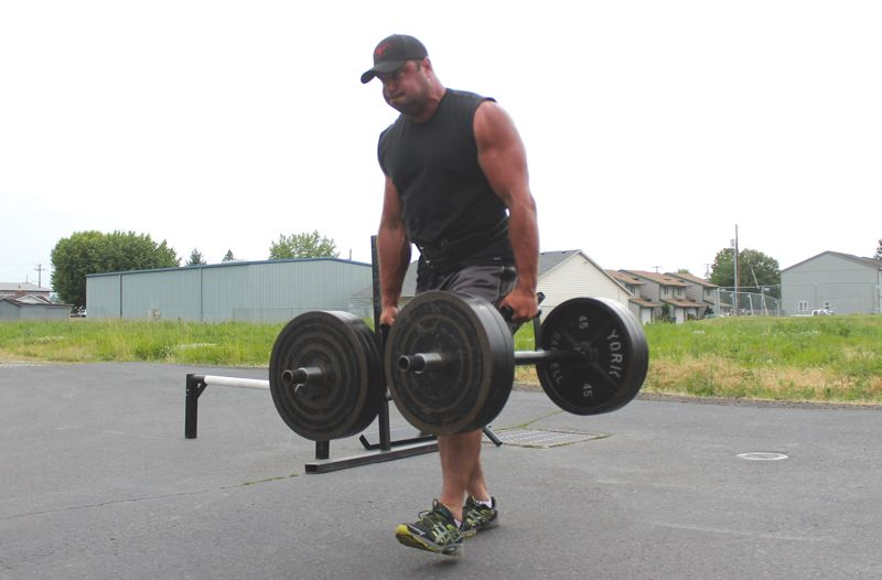 by: PAMPLIN MEDIA GROUP: JIM BESEDA - Jeff Rose carries bars loaded with 290 pounds in each arm across the parking lot at Cutting Edge gym in Molalla.