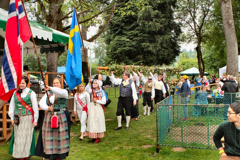 by: DAVID F. ASHTON - The procession of flags from Scandinavian countries leads the men carrying in the Maypole in this years Midsummer Festival in June in Oaks Park.