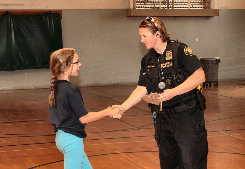 by: DAVID F. ASHTON - G.R.E.A.T. instructor and Transit Police Officer Kristi Butcher awards a student from one of her classes at Hosford.