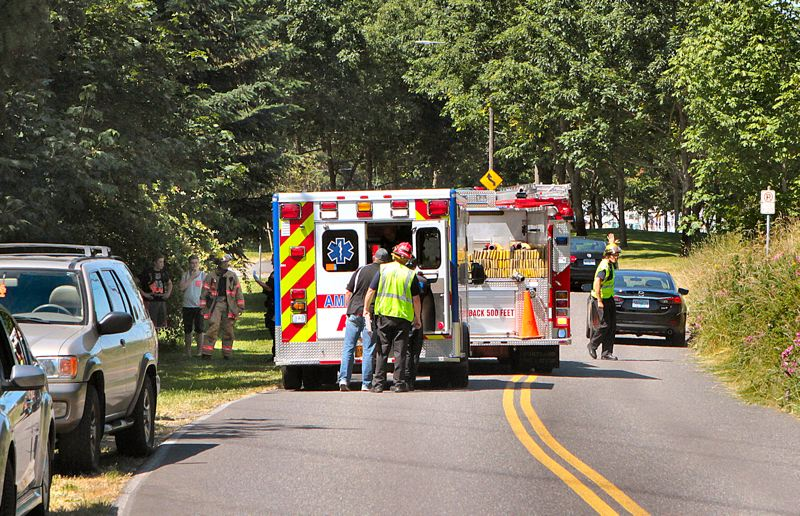 by: DAVID F. ASHTON - An unidentified adult looks into the ambulance thats about to transport a teenager hurt in the crash to the hospital.