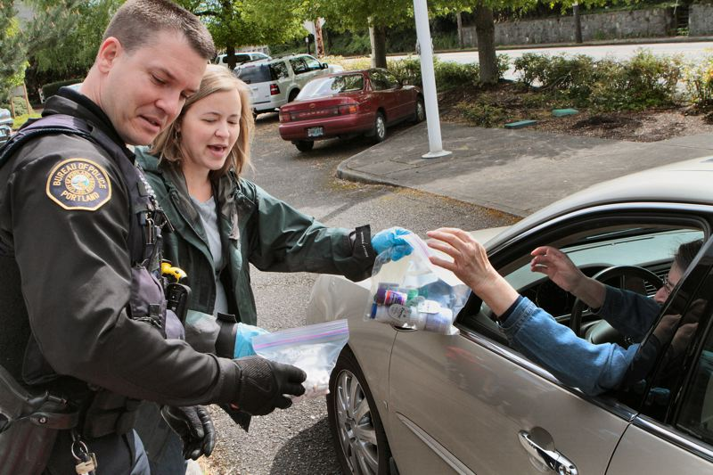by: DAVID F. ASHTON - Portland Police East Precinct Neighborhood Response Team Officer Rob Brown, and City of Portland Office of Neighborhood Involvement Crime Prevention Specialist Jenni Pullen, receive unused medications from a Southeast resident.