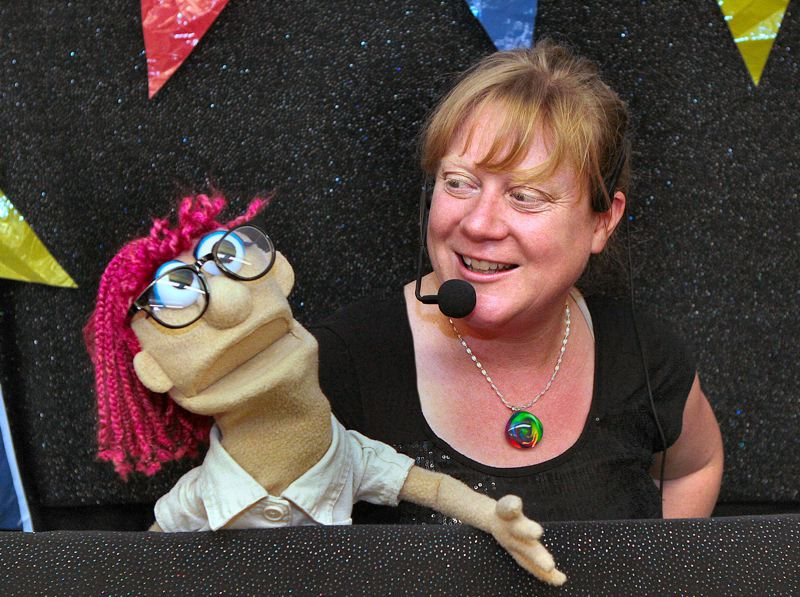 by: DAVID F. ASHTON - Gabby the Librarian is the host of the Library Sesquicentennial Celebration, aided by puppeteer Penny Walter, seen here at the Sellwood Branch Library.
